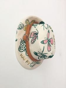 Cappello beige con cinta marrone e stampe farfalle verdi e rosa