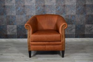 Poltrona vintage in pelle invecchiata color cuoio e borchie