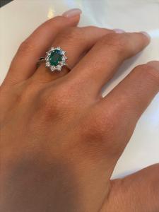Anello montatura oro bianco impreziosito da Smeraldo centrale e corona di diamanti